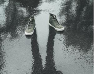 Paire de chaussures vides projetant l'ombre d'un homme sur le sol mouillé