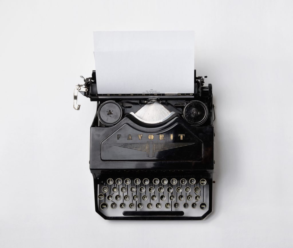 Machine à écrire noire contenant une page A4 blanche